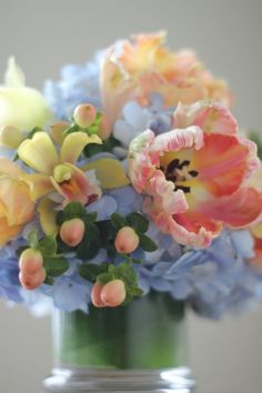 tulip and orchid, hydrangea or delphinium in a peach, yellow, and blue flower arrangement