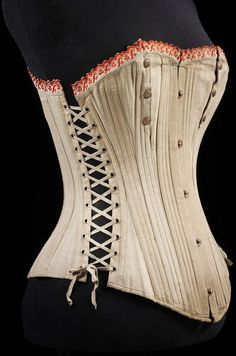 Pair of ladies corsets, possibly for maternity, made of cream cotton with red machine-embroidered trim.