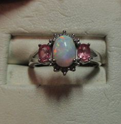 Ladies sterling silver genuine firey opal with two pink topaz at .50cts on the sides and six diamonds at the ends at .03cts. It measures 10mm across the top of the stones and ring and is a size 7 and can easily be sized by any fine silversmith. This is a beauty in sterling silver.