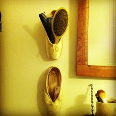 I finally came up with something to do with my old pointe shoes! Re-purpose them as little wall containers! Here I've used one to hold some combs and a hair brush & one to hold my lip gloss. This would also work really well for pens/pencils/office supplies, hair accessories, etc...