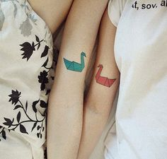 Pareja recostados en una cama mostrando sus tatuajes en forma de pájaros de papel de origami