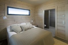 Bedroom with natural colour scheme. Log walls Paneeli-Ässä 1600 white, Tikkurila. Honka holiday homes.