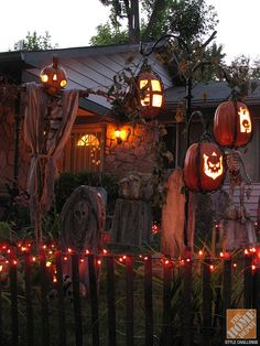 DIY Halloween Yard Decorations: Faux pumpkins become lanterns when carved and hung from the trees