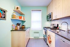 Laura's kitchen renovation features custom maple cabinets, translucent subway backsplash tiles, and a cheery aqua paint finish to brighten the room.