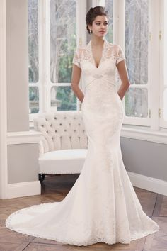 M1301Z - Lace slim A-line wedding dress with Queen Anne neckline. Bodice features a V-neck cap sleeve lace overlay and a banded empire waist with jeweled detail. Chapel length train.