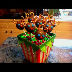 Cake balls dipped in chocolate with pretzel antlers, M&M; eyes, and a red M&M; Rudolph nose on a skewer!