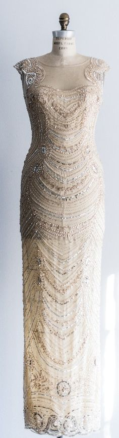 Beaded gown with gold beading over cream net with nude lining. Illusion neck and back with center back splits.