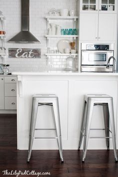 subway tile + open shelving + white cabinetry + wood flooring + metal stools