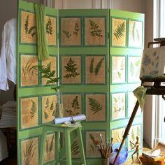 Un paravent en bois décoré de fougères et de feuilles manuscrites