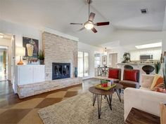 Living room with fireplace, hardwood floors, and open layout 9920 Chukar Bnd, Austin, TX 78758