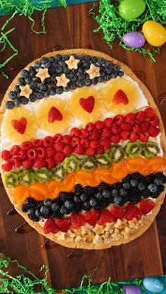 This adorable and easy Easter egg fruit pizza is the only sweet treat we need this Spring. Inspired by classic Easter eggs, we'll show you how to decorate a store-bought sugar cookie base with creamy frosting and fresh fruit. Decorating this colorful Easter dessert is almost as fun as eating it! #easterrecipe #fruitpizza #creamcheesefrosting #recipe #bhg