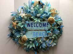 """FOR SALE...($120) Deco Mesh """"Welcome To The Beach"""" Wreath. Wreath is 26""""x26""""x6""""deep. It is made with wire frame, burlap mesh, blue mesh ruffles, ribbons, wood sign, wood flip flops, glass turtles and of course sea shells. If you are interested, in box me for more details!"""