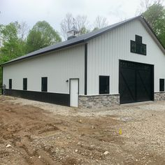 This pole barn storage building is set back on top of a hill in a wooded area in Central Ohio. The building features white sidewalls with black trim. Pole Barn Shop, Metal Pole Barns, Pole Barn Garage, Building A Pole Barn, Pole Barn House Plans, Metal Barn, Pole Barn Homes, New House Plans, Cabin Plans