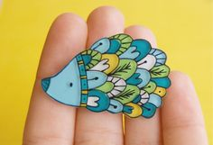 A hand sawed hedgehog brooch from 2mm thick plexiglass, hand illustrated and hand painted and with one thick layer of triple gloss to protect the color and ink.  It is measures approximately 4 cm x 3 cm (1.5 x 1.2 inches).  It comes in a gift box and can be shipped worldwide.    *************************************************************    Please read my SHOP POLICIES page before purchasing.  http://www.etsy.com/shop_policy.php?user_id=5341694    Choose your currency at...