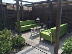 Groene tuinmeubelen met rvs en allweather stof op houten vlonder.