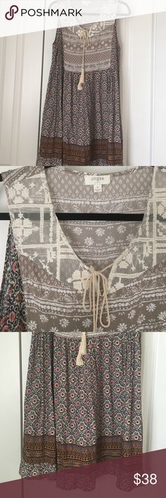 Umgee Patterned Sleeveless Dress 'Umgee' Patterned Sleeveless Dress. Light and flowy dress with flower pattern and Aztec print near bottom hem. Lace material near neckline with a string tie. Umgee Dresses Midi