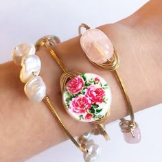 """Mother of Pearl Pink Rose Wire Bangle Includes (1) bangle made with genuine mother of pearl stones & gold colored wire.  MOP stones have pink roses with green leaves printed on them. Wire is tarnish resistant. Diameter is 2.75"""" across.  Note: Other bangles shown are for styling suggestions only, and are not included. Because these are natural stones, there will be slight color/shape variations, as no two stones are the same.  Sydney Elle Jewelry Bracelets"""