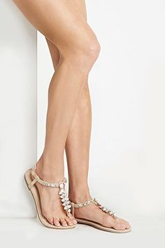 Style Deals - A pair of flat faux leather sandals with a T-strap, a rhinestone-encrusted flower design, and a buckled ankle strap.