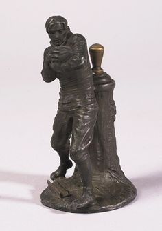 """Rare football figural lighter c.1900. Great white metal figural player holding melon style ball with orig. weathered bronze patina. Retains orig. strike stick in back, 4"""" tall. One of the earliest pieces of figural football materials that we've seen. $1650"""