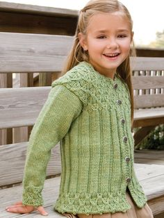 """Wickerwork cabling enhances the bottom, cuffs and yoke of this toasty ribbed cardigan. This e-pattern was originally published in the January 2011 issue of Creative Knitting magazine. Size: Includes girls 2 through 10. Made with medium (worsted) weight yarn, size 7 (4.5mm) 24"""" circular and double-pointed needles, and size F (4mm) crochet hook. Skill Level: Intermediate"""