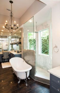 A remodeled master bathroom shows off all the bells and whistles with a beautiful bathtub and walk-through shower. The space was reworked to add new closets and vanity areas. A courtyard with wall of ivy offers privacy to the space.