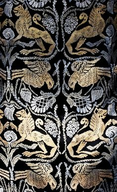 A Maria Gallenga stencilled velvet medieval style dress, circa 1925. the black silk velvet printed overall in gold and silver with birds and lions, with gold lame lined hanging sleeves