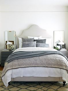 Warm white walls brighten this bedroom, while layers and layers of blankets, throws, and pillows make the bed the focus for a retreat that feels snug but not cramped.