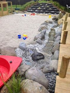 Stream bed alongside huge sandpit. Locate your sandpit near a tap or water tank for easy access to water.  Fill the sandpit to a recommended depth of 600mm.  Enclose your sandpit in decking, stones or stumps to provide a place for play.  Build your sandpit in a shady spot ensure that you have effective drainage.  Consider climbing plants on a timber frame for added shade