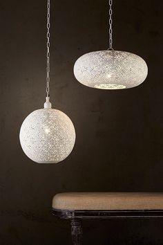 Perforated white pendants with a white interior, providing an exotic feel through the delicately patterned filigree.