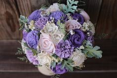 This listing is a bouquet featuring roses, gardenias, chorkis, carnations and zinnias in an array of light to medium shades of purple and blush pink. Simply sweet! This bouquet has cream filler and soft, preserved caspia, faux dusty miller and tallow berries. It is wrapped in burlap