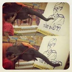 Thai elephant is painting the image of the King of Thailand as well as writing in Thai