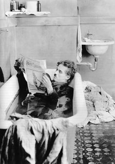Charlie Chaplin reading in the tub