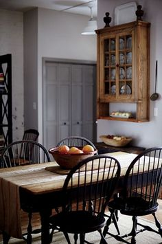 Feel at home in a modern country manor by combining rustic and natural textures. Love the black windsor chairs.