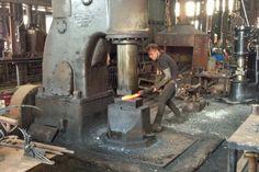 Artist Peter Mattila creates a sculpture using equipment in Launceston's old railways workshop.