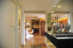 Apartamento localizado no Alto do Boa Vista/SP O piso de madeira aconchegante está presente no chão do apartamento que combina com o detalhe do ladrilho hidráulico no hall de entrada. Para dar amplitude ao hall, um espelho na parede com um aparador suspenso da todo um charme ao apartamento.