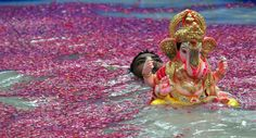 """""""An Indian Hindu devotee carries an idol of elephant-headed Hindu god Ganesha for immersion inside an environmentally friendly artificial water tank on the fifth day of the ten-day long festival Ganesh Chaturthi, in Mumbai on September 13, 2013."""""""