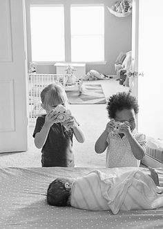 Say cheese! Two little girls click away with their toy cameras moments after meeting their newborn sister for the first time.
