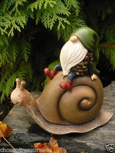 """Cute little """"acorn"""" style gnome hanging on to a slow walking snail. Garden gnomes are popular in gardens, or as a collection. Fun little people!"""