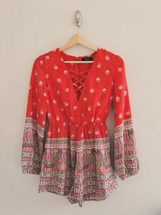 Long sleeve lace up front elastic waist border print romper. 100% Polyester