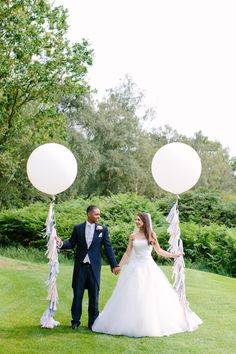 Bride & Groom photography with giant balloons and tassel tails -   Image by Hayley Savage Photography - Bride wears Maggie Sottero & Bridesmaids wear No.1 by Jenny Packham. Pink, White & Grey colour scheme & Photography by Hayley Savage.
