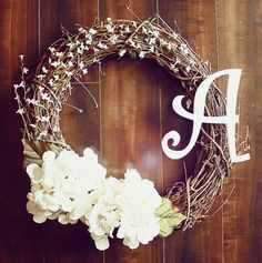 simple grapevine wreath with white silk hydrangeas and small silk white flowers with wooden initial plaque attached