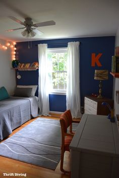 Behr Mosaic Blue boys bedroom makeover features an accent wall and orange accents, with white curtains. This bedroom is perfect for tweens and teen boys. Blue Boys Bedroom, Boy Bedroom Design, Blue Accent Walls, Bedroom Makeover, Kids Shared Bedroom, Blue Bedroom Ideas For Couples, Tween Bedroom Makeover, Tween Boy Bedroom, Kid Room Decor