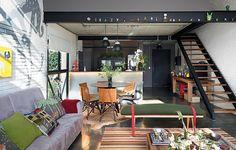 A cozinha americana fica logo na entrada do apartamento com decoração da arquiteta Bruna Riscalli. A marcenaria segue o tom escuro das paredes, dando um visual masculino e moderno