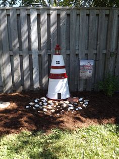 Flower Pot Lighthouse. I took 3 of my existing pots (bottom 2 are plastic and top is clay for weight) spray painted and added an old ikea lantern painted to match. A collection of shells from a recent trip around the bottom and it makes a nice addition to a blank spot in the garden.