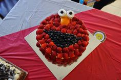 Made a vanilla cake iced it with fresh cream icing and decorated it with strawberries, blueberries(mouth), marshmallows(eyes) n orange peel(nose). Did this for my son's third bday because Elmo was his favourite character and strawberries his favourite fruit.