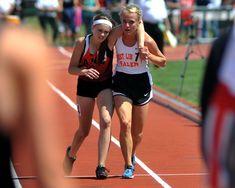 """Meghan Vogel, carregada pela competidora Arden McMath, ultrapassa a linha de chegada após ter caído durante a corrida."""