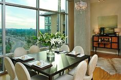 The clean lines and light colors of this open-concept dining room harmonize with the natural brightness of the space. The design guides the eye toward the high windows through which you have a fantastic view of the Tennessee hills. Downtown Nashville penthouse design by Dana Goodman Interiors. www.danagoodmanin... #InteriorDesign #Interior #Design #Designer #Nashville #citylife