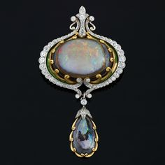 Opal, Diamond, Platinum and Gold Brooch-Pendant by Marcus & Co. Circa 1900.  An American Art Nouveau 18 karat gold and platinum brooch/pendant with opal, diamonds and enamel by Marcus & Co. The brooch/pendant has a center cabochon black opal and 76 old mine-cut diamonds with an approximate total weight of 4.00 carats.The center opal is mounted in a scrolled setting and framed with enamel and diamonds, suspending a matched scroll set opal.