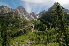 """Grand Tetons and waterfalls. The National Park Service reports, """"The elevation of the park ranges from 6,320 feet on the sagebrush-dominated valley floor to 13,770 feet on the windswept granite summit of the Grand Teton. Between the summit and plain, forests carpet the mountainsides."""""""