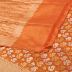 "The ""#Orange"" #handwoven #Banarasi #Silk #Sari from Shivangi Kasliwal is woven gold and silver zari floral motifs all over the body that is set off by a gold zari banarasi border on either side. An attractive gold zari zig-zag weaves banarasi pallu adorn the sari. The border is repeated on the orange blouse that completes the sari."